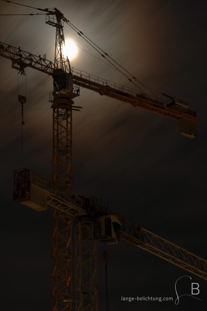 Zwei Kräne bei Vollmond auf einer Berliner Baustelle. Durch die verwischten Wolken hindurch scheint der Vollmond.