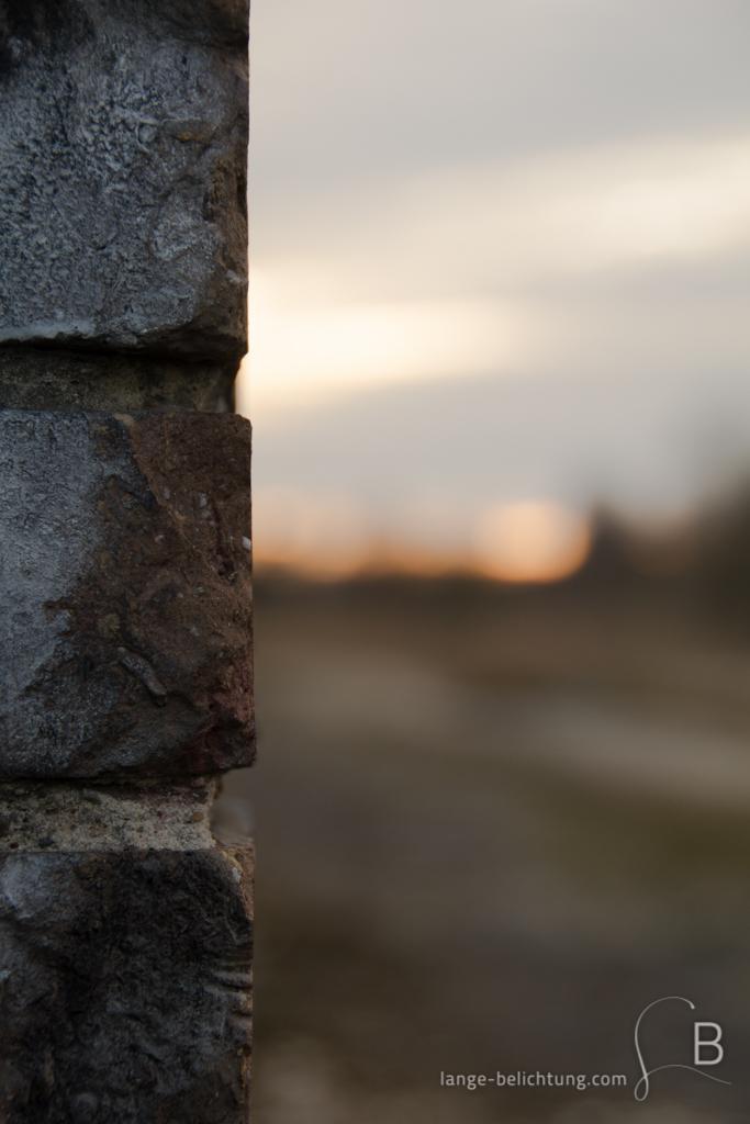 Nahaufnahme einer Backsteinmauer. Im Hintergrund sieht man eine große Freifläche. Am Horizont taucht die Sonne den Himmel in oranges Licht.