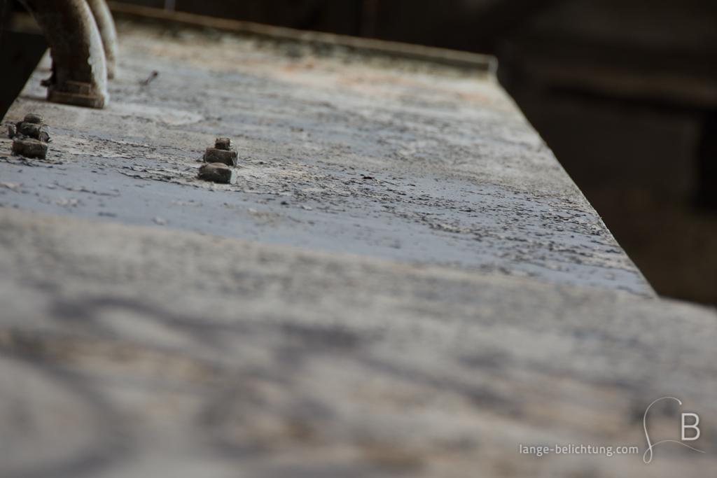 Von einem Stahlträger platzt die Farbe ab. Im Fokus stehen wir verrostende große Muttern, die an dem Stahlträger befestigt sind.