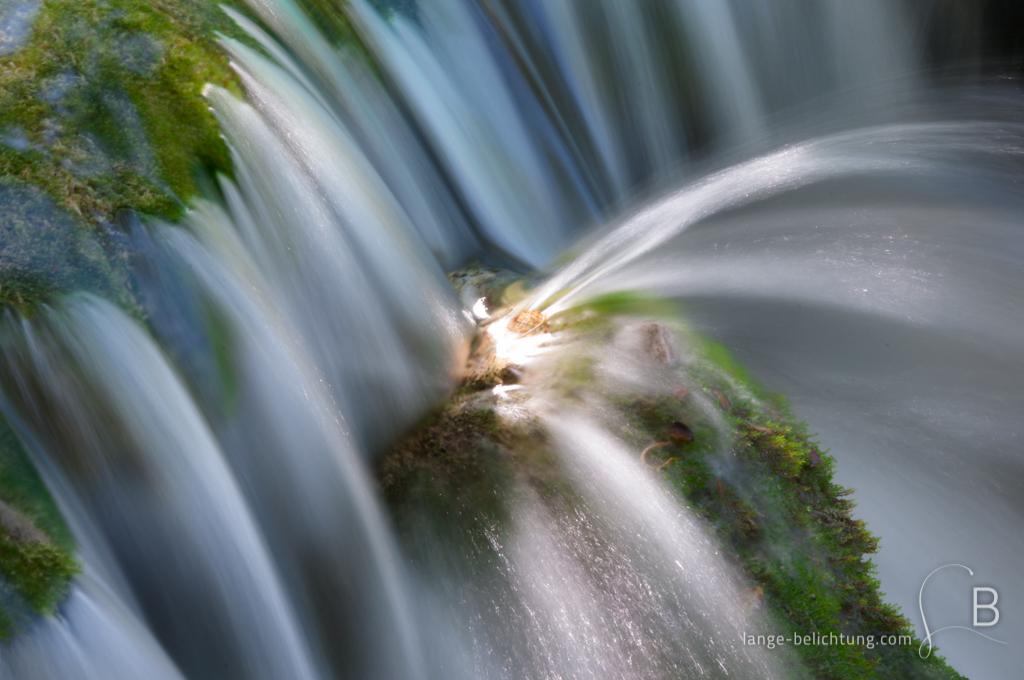 Ein Wasserfall läuft über Moos und wird von einem Felsvorsprung abgelenkt