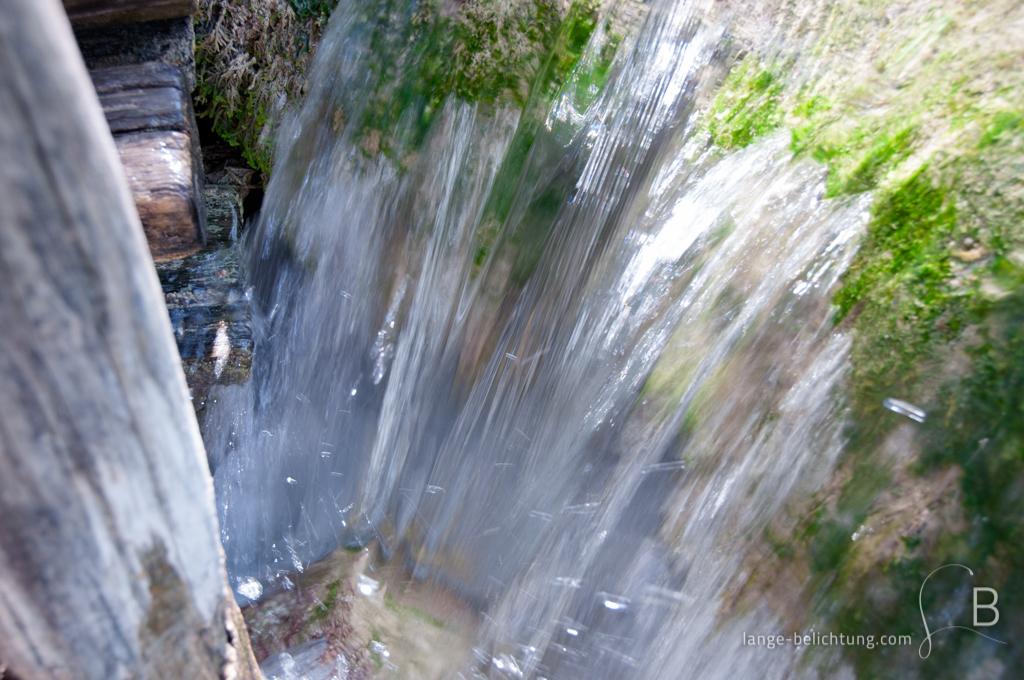 Direkt an einem Holzweg fließt das Wasser über Moos bewachsene Felsen