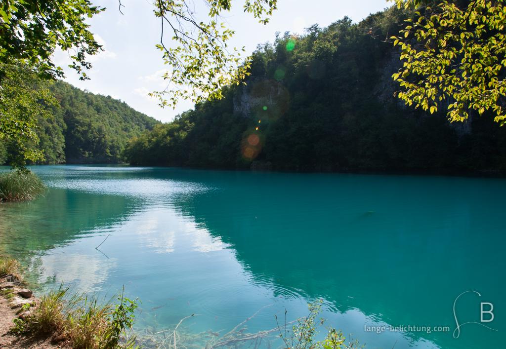 Zwischen den Bergen in Kroatien im Nationalpark Plivicer Seen erstreckt sich ein See zwischen Wäldern. Das Wasser an diesem sonnigen Tag schimmert türkis und reflektiert die Umgebung.