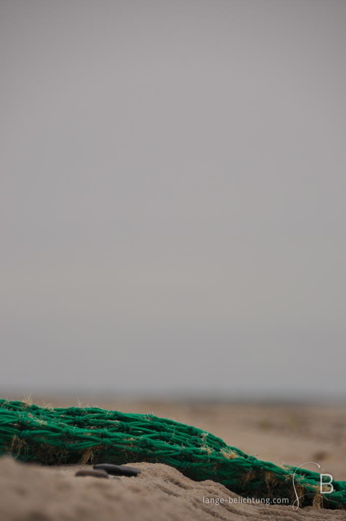 Ein Fischernetz liegt am Strand. Es ist altes Strandgut, dass nicht mehr benötigt wird.
