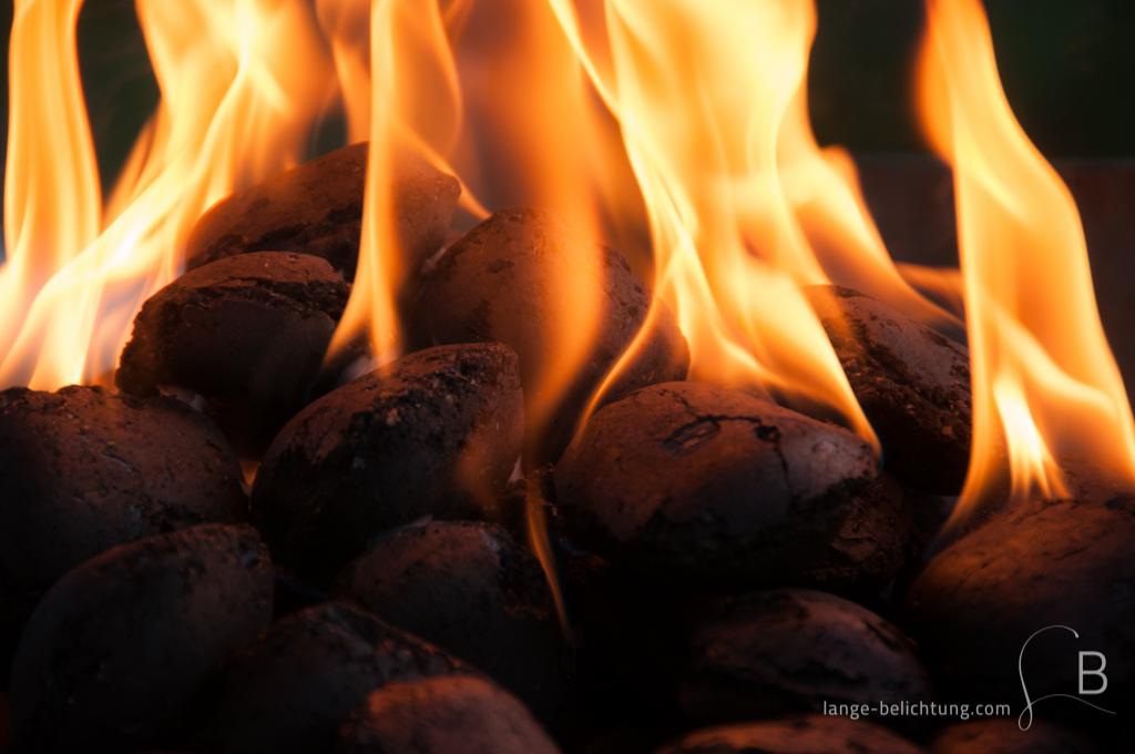 Grillkohle aus Holz wurde mithilfe von Grillanzünder angezündet. Die Kohle ist klar erkennbar ebenso die Flammen, die scheinbar um die Kohle herum lodern.