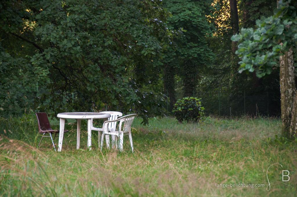 Zwei weiße und ein dunkelroter Stuhl stehen um einen weißen Gartentisch mitten auf der Wiese unter einem Baum. Es wirkt so, als würde man auf jemanden warten.