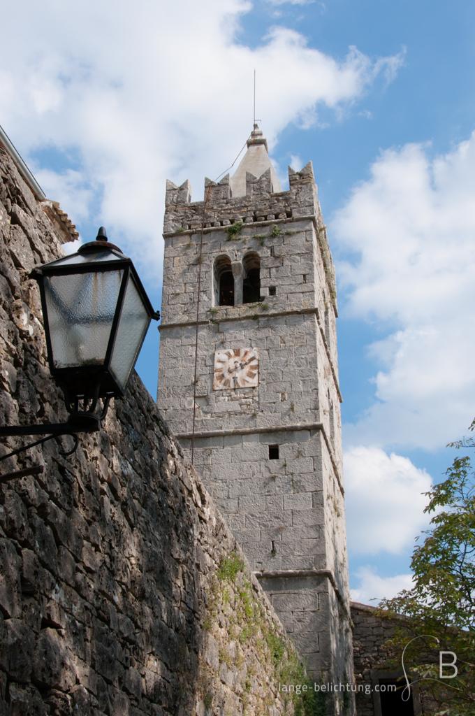 Der Kirchturm von Hum in Kroatien mit alter verrosteter Uhr. Im Vordergrund ist eine als Laterne an der Stadtmauer zu sehen.