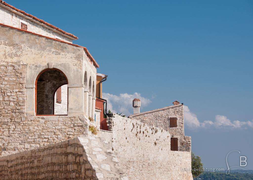 Ein weißes Haus mit Ziegeldach direkt am Meer. Am blauen Himmel finden sich ein paar Schönwetter Wolken.
