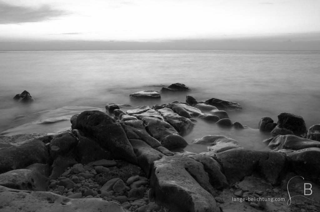 Die Sonne ist bereits untergegangen. Im Vordergrund sind Felsen im Wasser zu erkennen, die durch lange Belichtung wie von Nebel umschlossen wirken.