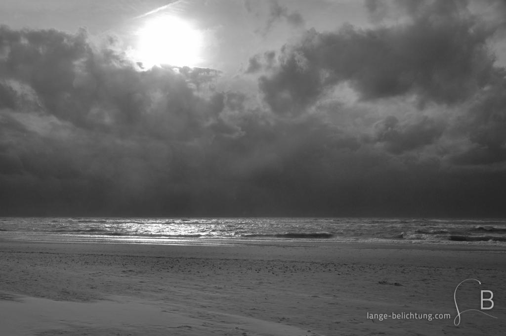 An der Nordsee Küste wird ein aufziehender Sturm von dunklen Wolken angekündigt. Der Strand ist menschenleer. Durch die Wolken bricht aber noch mal die Sonne und spiegelt sich im Wasser.