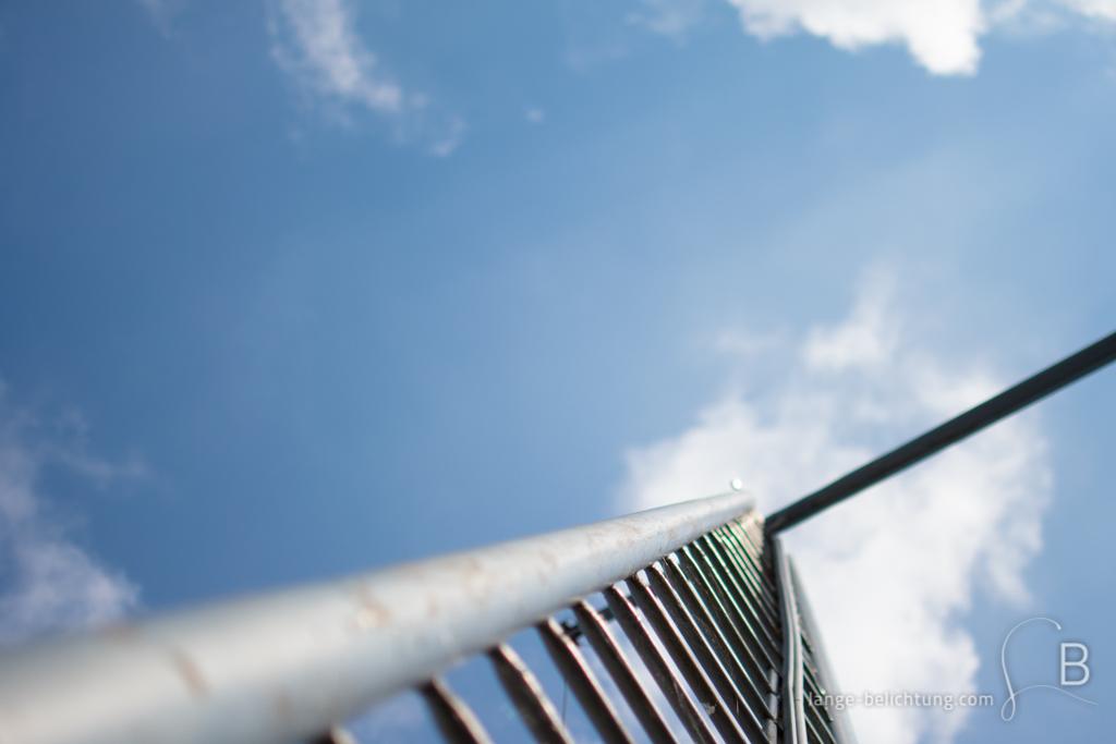 Foto von einer Leiter, die in den Himmel ragt. Der Himmel ist strahlend blau. Nur ein paar Wolkenfetzen sind zu sehen.