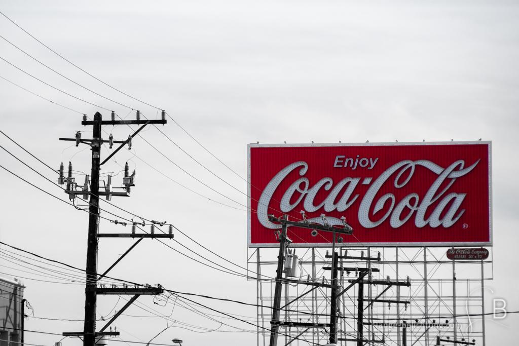 Eine Coca Cola Werbetafel hinter einer Vielzahl von Strommasten und Überlandleitungen an einer Straße.