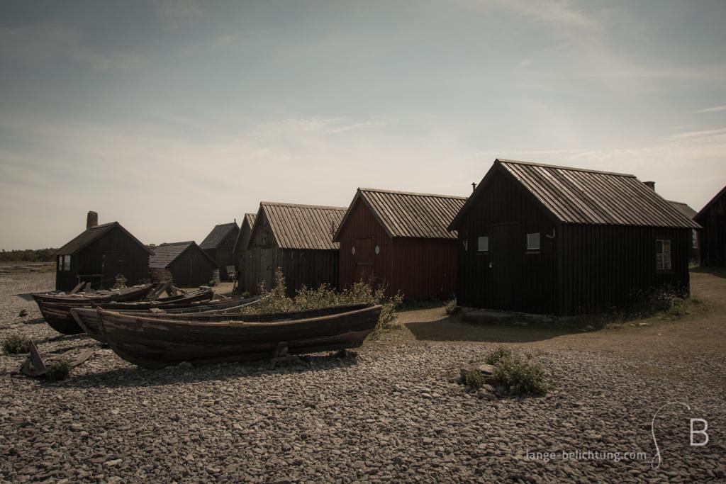 Ein altes schwedisches Fischerdorf auf Farö. Im Vordergrund liegen alte Fischerboote an Land. Dahinter stehen viele kleine Fischerhütten.