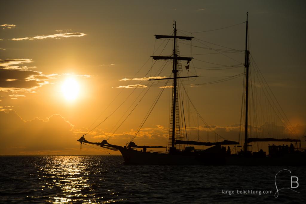 Die Sonne geht auf der Ostsee unter, während ein Zweimaster mit geborgenen Segeln als Silhouette im Vordergrund fährt. Die wenigen Wolken am Himmel sind von der Sonne orange gefärbt.
