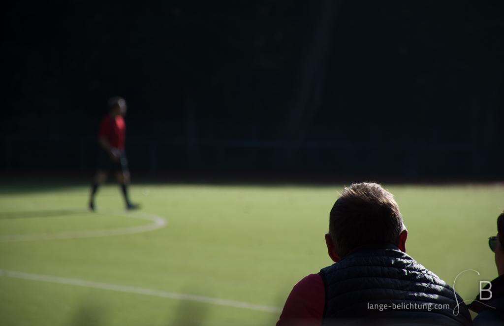 Ein Zuschauer beobachtet den Schiedrichter in rot, der allein über den Kunstrasenplatz bei einem Fußballspiel läuft.dd