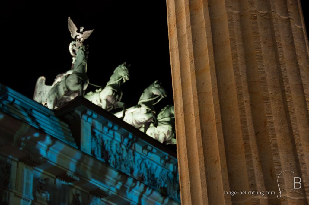 Die angeleuchtete Quadriga strehlt über dem Brandenburger Tor. Im Vordergrund des Bildes ist eine Säule des Seitenbaus am Brandenburger Tor zu sehen.
