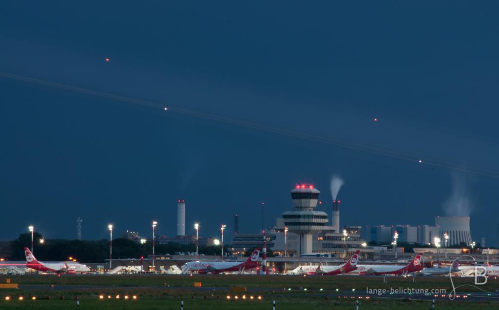 Der Flughafen Tegel bei Nacht. Im Hintergrund erkennt man das Kraftwerk in Spandau. Ein Streifen lässt ein vorbeifliegendes Flugzeug erkennen.