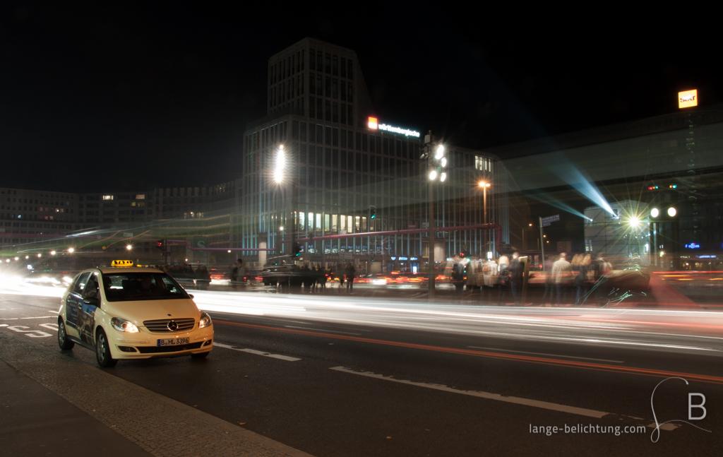 Ein Taxi steht am Potsdamer Platz und wartet auf Fahrgäste während drumherum das Leben pulsiert.