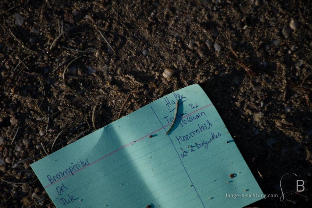Eine handgeschriebener Einkaufszettel liegt achtlos weggeworfen auf dem Boden.