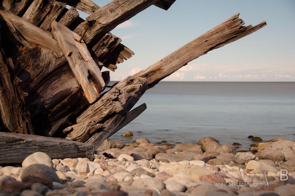 Vor langer Zeit ist auf einer schwedischen Insel ein Segelschiff auf Grund gelaufen. Das Wrack sieht man im Vordergrund während im Hintergrund die Spiegelglatte Ostsee zu erkennen ist.