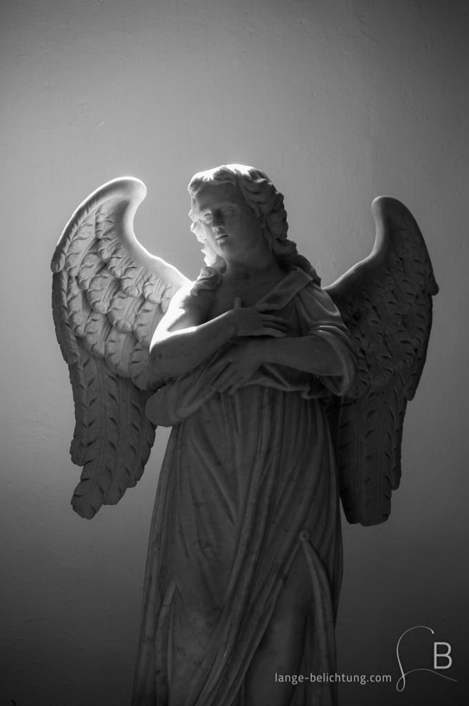 Ein Engel steht in einem Seitenschiff einer Kirche. Durch das Fenster fällt Licht auf den recht dunklen Raum und strahlt einen Teil des Flügels an.