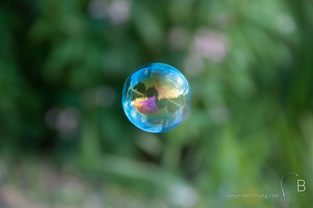 in einer Seifenblase spiegelt sich die Umgebung in schillernden Farben von blau über gelb zu violett.