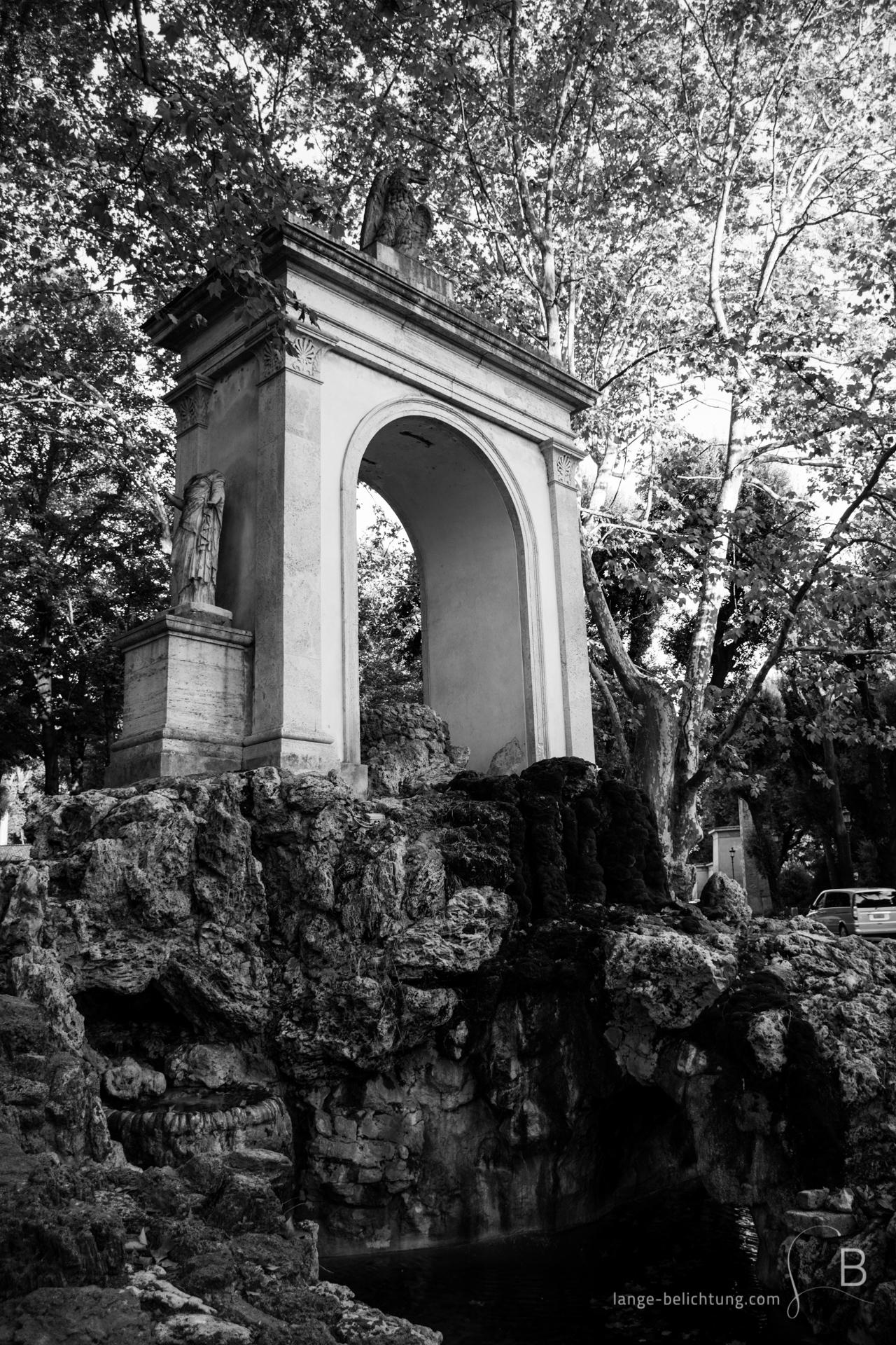 Abgebildet ist ein Brunnen in Rom nahe der Villa Borghese zwischen herbstlichen Laubbäumen. Das Bild in schwarzweiß zeigt die Fontana di Esculapio.