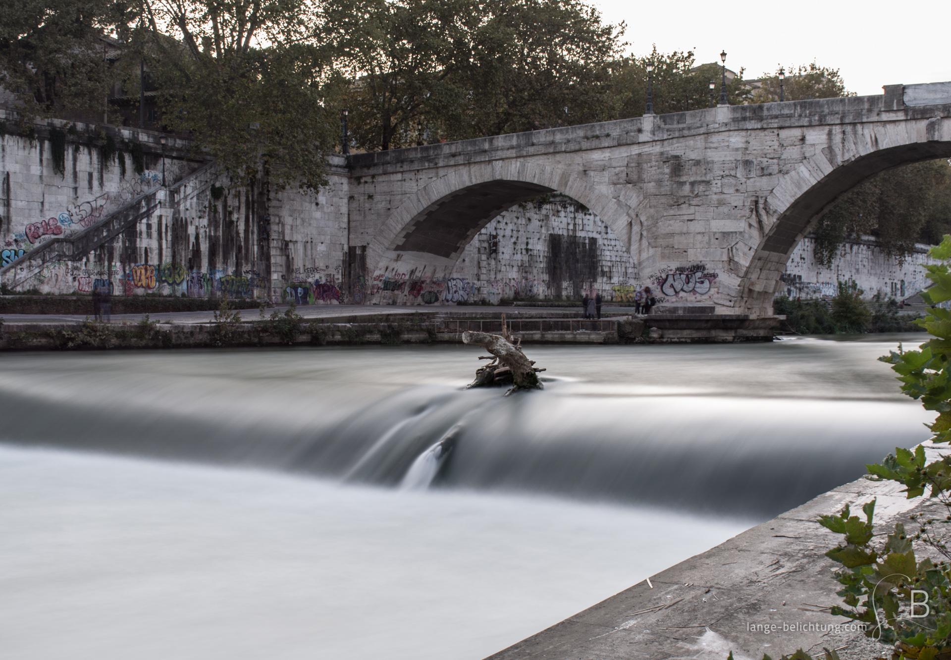 Eine Brücke, die übersäht ist mit Graffiti, führt über den Fluss Tiber zur Tiberinsel. Im Vordergrund ein kleines Wehr, dass das Wasser schneller fließen lässt. Kurz vor dem Wehr steckt ein Baumstamm